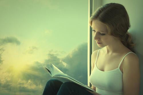 Kvinde læser bog ved vindue