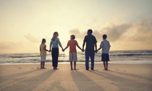 Familie hånd i hånd på strand