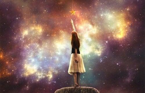 kvinde rækker ud efter stjerner