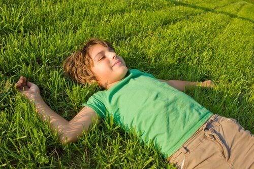 Dreng på græs er afslappes og i kontrol over hans følelser