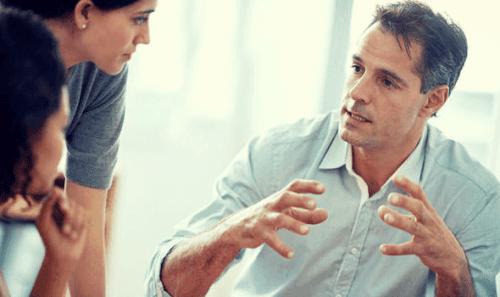 Mand diskuterer med kvinder og prøver at sige sin mening