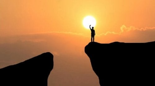 mand på klippe, rækker ud efter solen