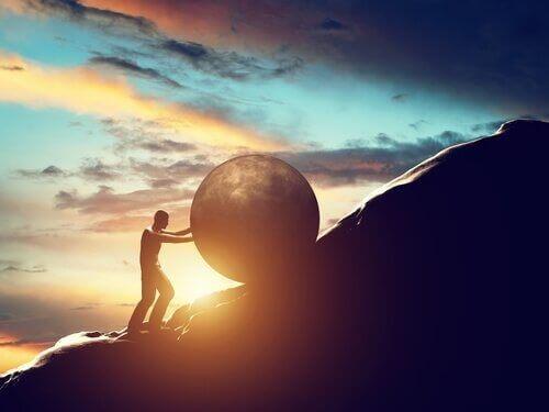 Mand der skubber en sten op af et bjerg