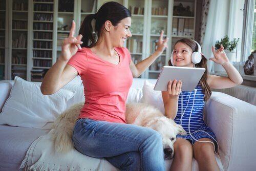 En mor og datter griner og synger sammen for at styrke forhold til børn