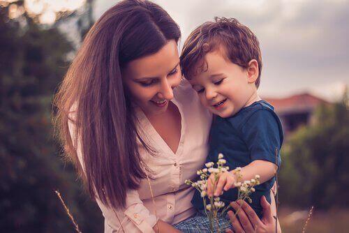 Kvinde med søn kigger på en blomst