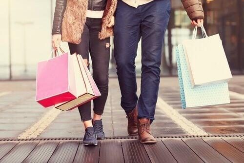 Personer med indkøbsposer symboliserer forbrugerisme