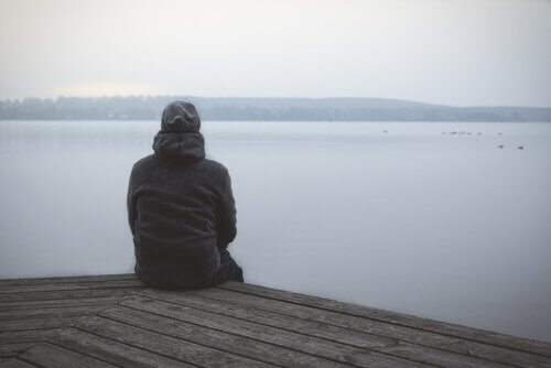 En mand sidder og kigger ud på søen