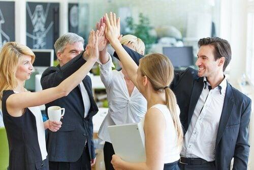 Kolleger giver fælles high five på grund af arbejdsplads engagement