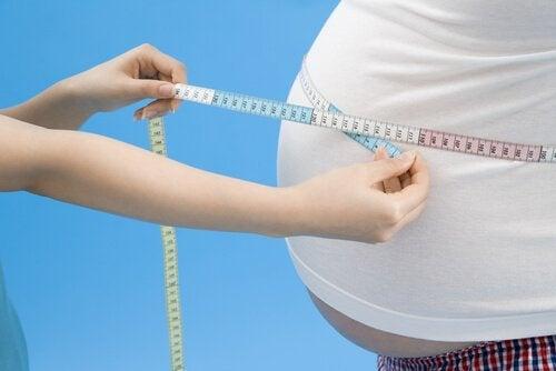 Fedme i fjernsynet er illustreret af kvinde, der måler stor mave