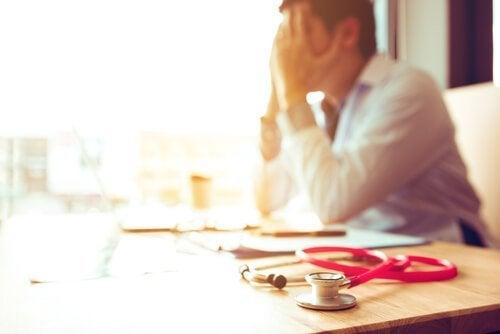 Træt mandlig læge symboliserer udbrændthed hos ansatte
