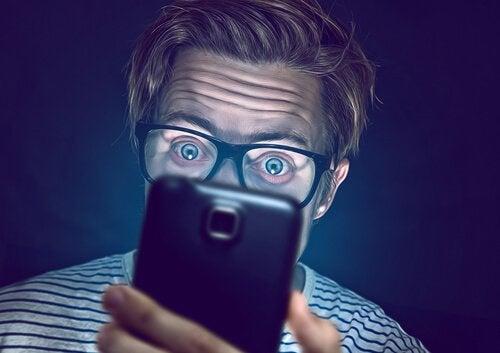 mand oplyses af sin skærm fra telefonen