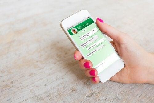 Kvinde med telefon i hånd er afhængig af WhatsApp