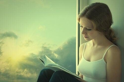 Kvinde læser bog i vindue