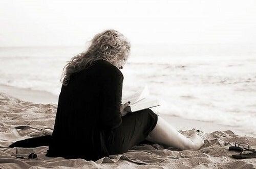 Sådan kan litteratur og poesi hjælpe vores velbefindende, når vi læser som denne kvinde på en strand