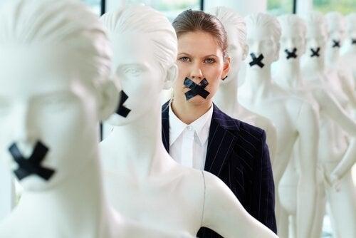 Kvinde med tape over munden omringet af dukker