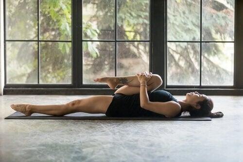 Kvinde på gulvet laver øvelser mod rygsmerter