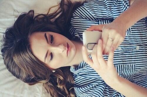 Kvinde på seng med mobil