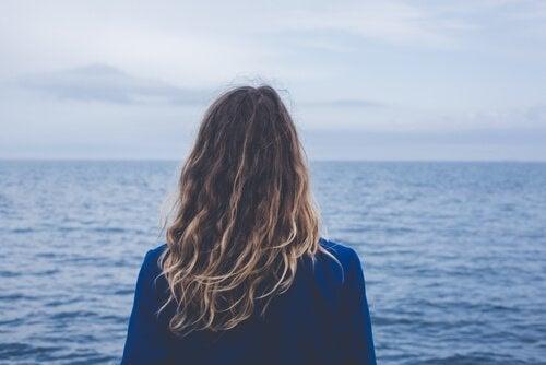 En kvinde ser ud over havet