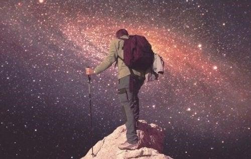 Mand på bjergtop foran universet illustrerer, at du skal tro på dig selv for at nå toppen