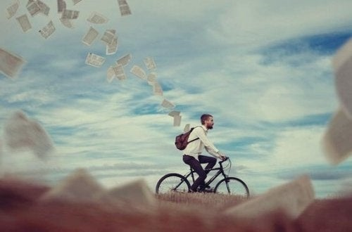 Mand på cykel, der taber en masse papirer