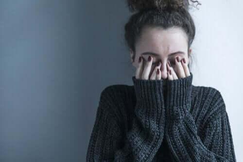 kvinde, der sidder op ad væg med hænder foran ansigt