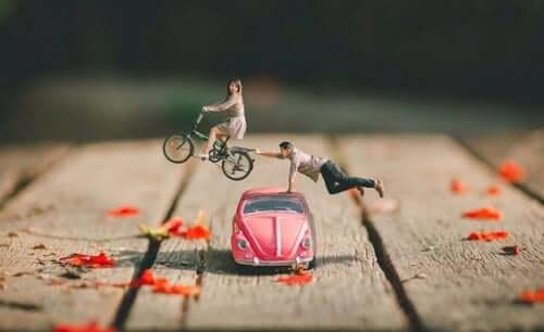Figur af par, hvor mand rækker ud efter flyvende kvinde på cykel