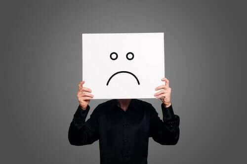 person med papir med sur smiley foran sit ansigt har valgt at være pessimist
