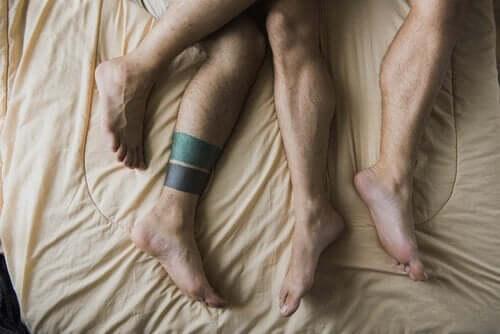 To mænds ben i seng illustrerer kammeratsex