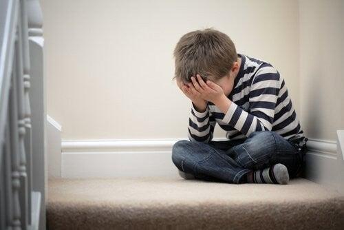 Dreng sidder på en trappe og er ked af det