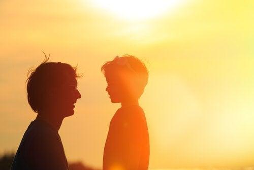 Far taler med søn foran sol