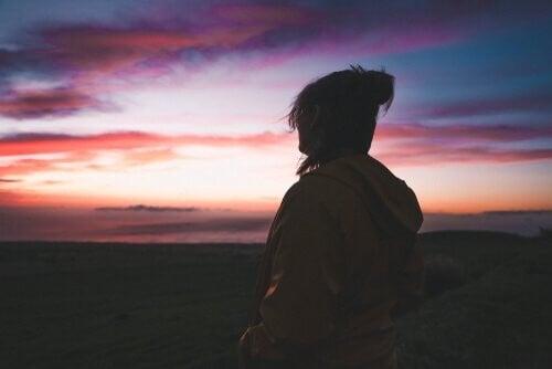 Kvinde kigger på en flot og farverig aftenhimmel