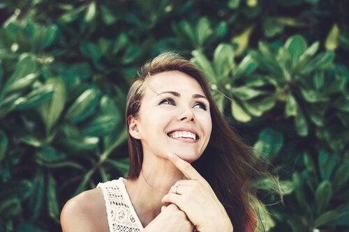 Smilende kvinde forstå, at være positiv er godt for dit selvværd