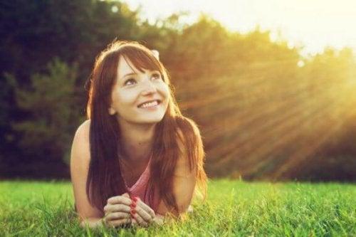 En kvinde smiler og kigger op mod solen