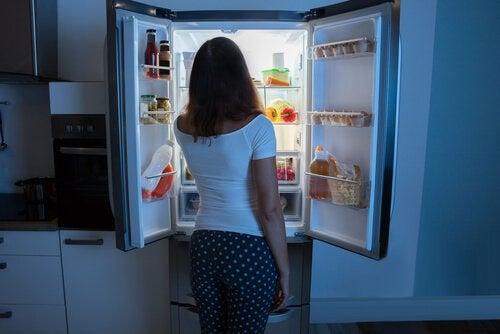 kvinde foran et åbent køleskab er nattespiser