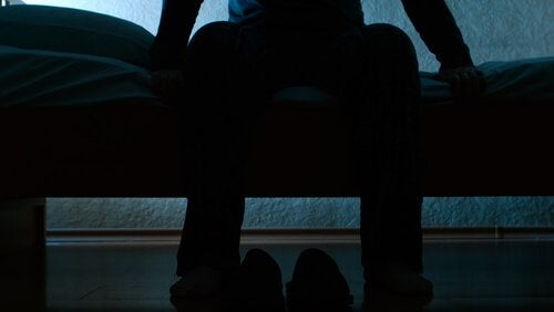 Mand sidder på sengen og lider af rastløse ben