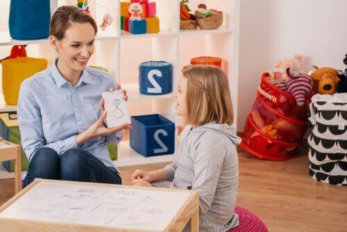 Kvinde hjælper pige med at overvinde sprogvanskeligheder hos børn