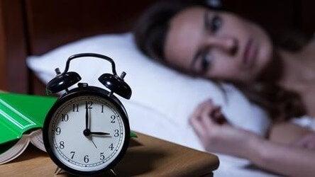 Kvinde, der kigger på ur, kan ikke sove