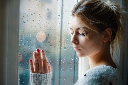 En kvinde med negative følelser står ved vindue