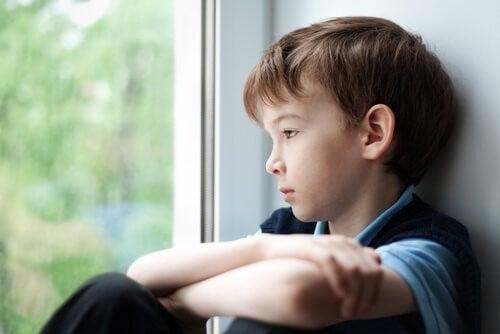 En trist dreng kigger ud af vinduet