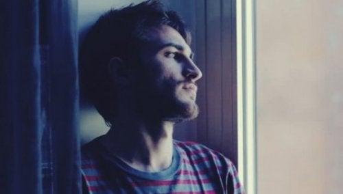 Trist mand kigger gennem vinduet og forsøger at finde sit indre selv