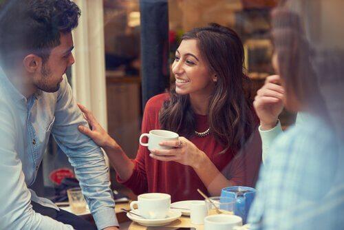 Smilende kvinder rører ved mands arm som tegn på, at hun er til at stole på