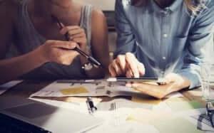 To personer sidder og kigger på dokumenter sammen