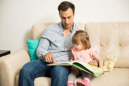 Far læser bog med datter i sofa som symbol på epigenetik