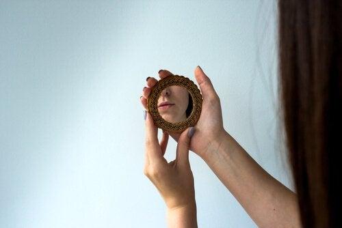 kvinde ser sig i et lille spejl