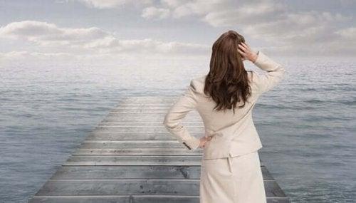 Kvinde står ved bro i hav