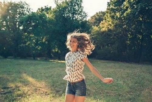 Glad, hoppende kvinde i have har ikke svært ved at vælge mellem tid eller penge