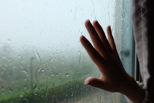 Kvinde lægger hånd på vindue med regn