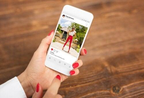 Psykologien bag Instagram illustreres af kvinde med telefon