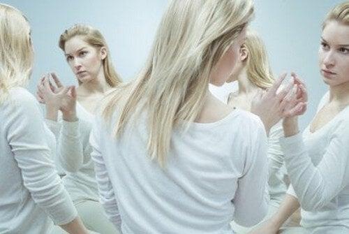 Kvinde, der ser sig selv i spejl, symboliserer de forskellige aspekter af selvet
