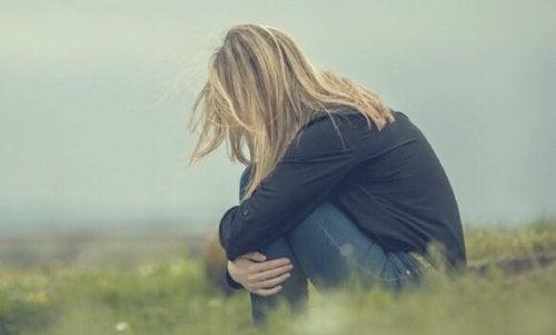 Person på mark krammer sig selv